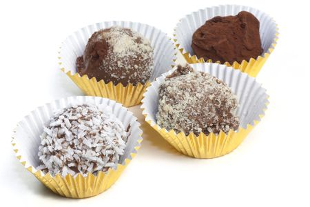 sitting on the ground: Homemade chocolate truffles with a variety of toppings such as cocoa, coconut, ground almonds.  Each sitting in a gold foil cup.