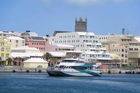 A Bermuda ferry cruising past the downtown waterfront of Hamilton, Bermuda.