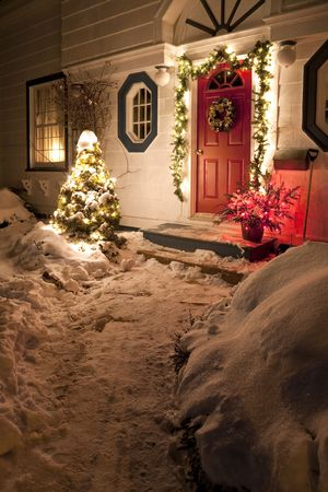 The front door of a snow covered family home decorated for Christmas. Stock Photo