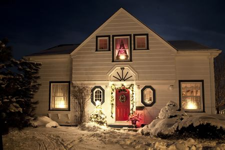 decoration: A house decorated with a wreath, garland and Christmas lights an a clear winter night. Stock Photo
