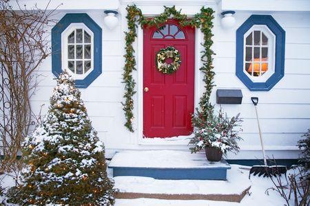 fachada de casa: Snow est� cayendo en el frente de una casa tradicional decorada para la Navidad con una corona de flores, guirnaldas y luces de Navidad.