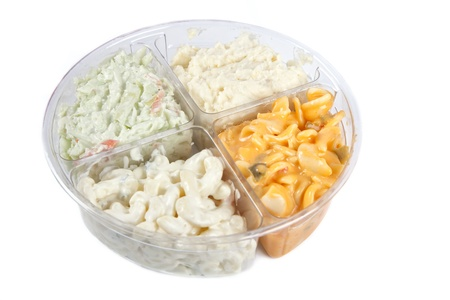 paczkowane: A premade packaged salad tray from the grocery store divided into four sections containing two types of pasta salad, a potato salad and a cole slaw.  Focus is on the center of the tray.  Object is not isolated.
