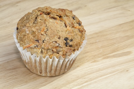 A healthy whole grain carrot raisin muffin with bran on a wooden surface.