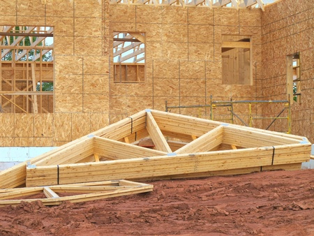 rafters: Construction of a new family home with bundles of rafters in the foreground.