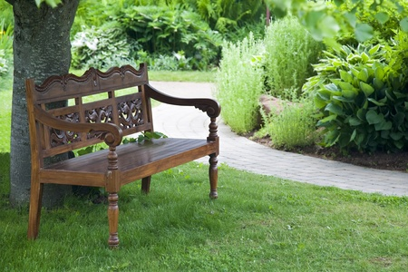 A carved teak bench in the shade of a tree in a tranquil garden.