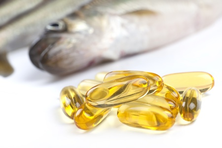 Close up of a  cod liver fish oil capsule, a nutritional supplement high in omega-3 fatty acids, EPA,  DHA, and  high levels of vitamin A and vitamin D.  Fresh fish are in the background. Stock Photo