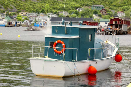 nfld: Small fishing or pleasure boat tied up at a wharf in a coastal outport on the island of NFLD, Canada.