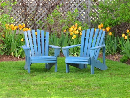 Blue wooden lawn chairs in the spring garden.