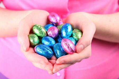 箔の一握りを保持している若い女性はチョコレートのイースターエッグ覆われています。