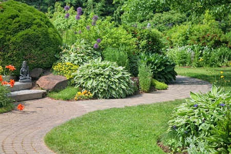 perennial: A stone walkway through a peaceful perennial garden. Stock Photo