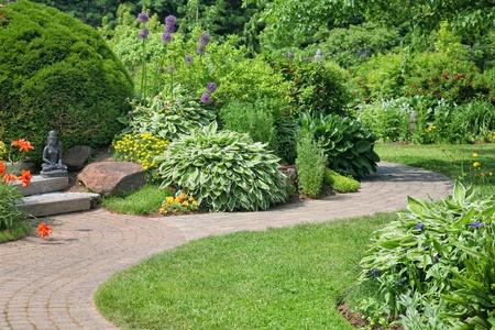 asian gardening: A stone walkway through a peaceful perennial garden. Stock Photo