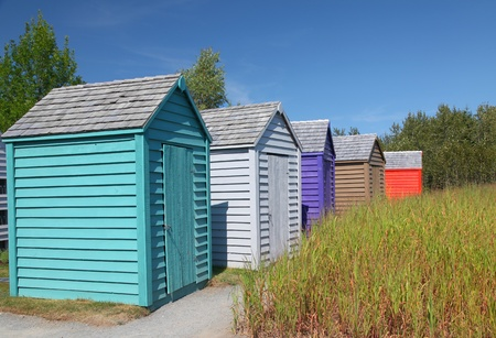 A row of brightly colored small garden sheds.