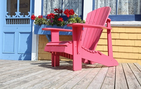 adirondack chair: Colorful Adirondack chair sitting on a patio or deck with a window box full of geraniums.