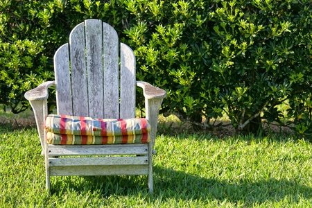 An old weathered Adirondack chair in the garden with a hedge as a backdrop.