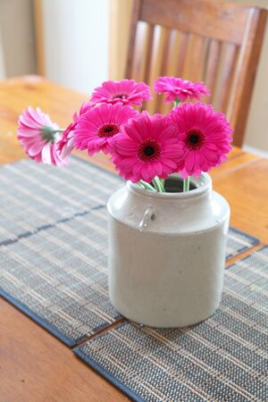 A bouquet of vibrant pink gerbera in an earthenware jug on a table. Stock fotó