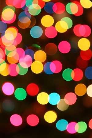 Multi colored Christmas lights out of focus on a dark background.