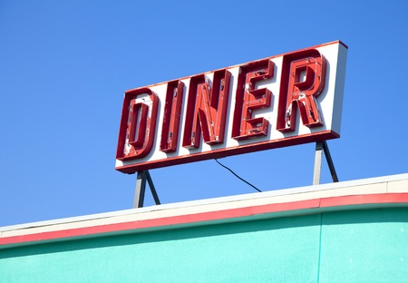 diner: An old retro diner sign on top of a building.