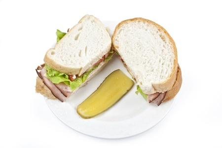 Fresh ham and cheese sandwich and a dill pickle served on a white porcelain plate. Stock Photo - 9838342