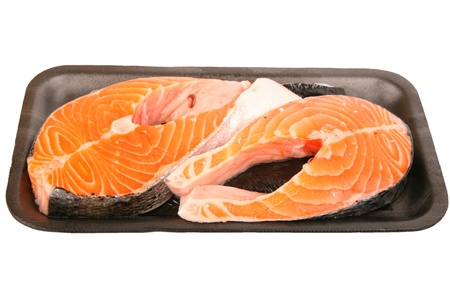 Two fresh Atlantic salmon steaks packed for the supermarket on a foam tray and wrapped in cellophane. Stock Photo