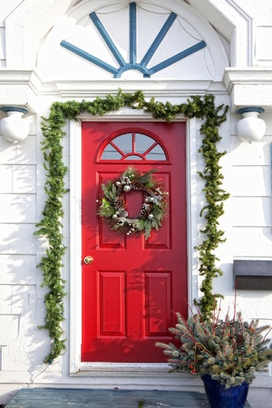 A door of am older home decorated for Christmas. Stock Photo