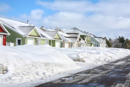 rowhouses: A row of rowhouses with deep snow banks pushed awy from the asphalt street.