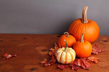 calabazas de halloween: Ca�da de calabaza y calabaza decorativo con hojas de oto�o en una mesa de madera.