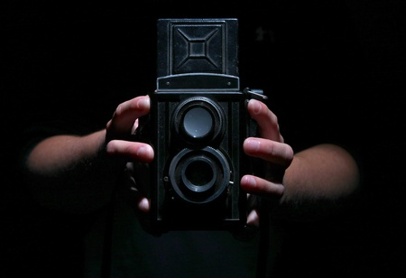 Vintage twin reflex camera held by two hands on black.