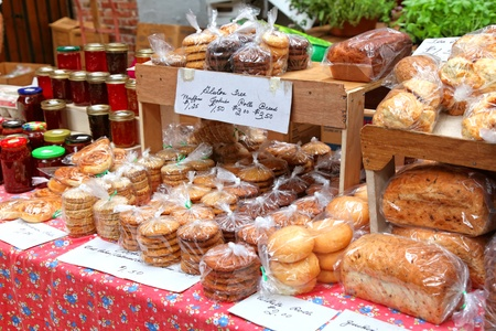 Baked goods and homemade preserves and jams at a farmers market.