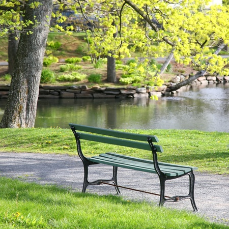 Empty wooden park bench overlooking a lake or pond in the Halifax Public Gardens, Halifax, Nova Scotia, Canada. photo
