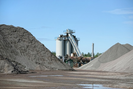 rock pile: An industrial asphalt plant surrounded by piles of gravel.