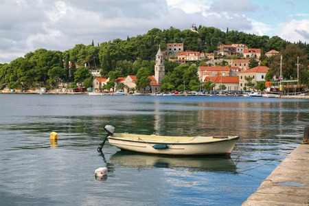 A small boat moored in a scenic medival fishing village along the coast of Croatia. Stock Photo