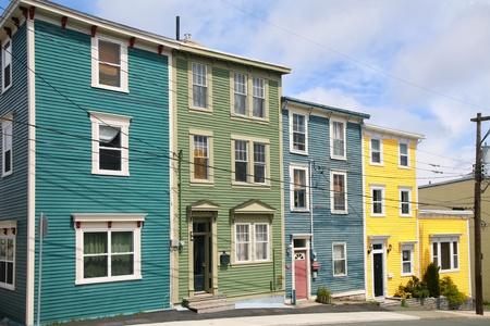 rij huizen: Traditionele houten rij huizen op de heuvelachtige straten van St. John Redactioneel