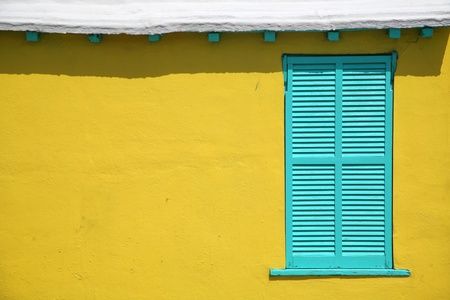 Contrasting window shutters against the interesting texture of a stucco wall of a traditional Bermuda cottage. Stock Photo - 10929841