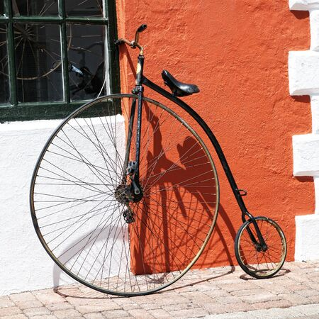 An antique bicycle leaning up against the stucco wall of a building. Stock Photo