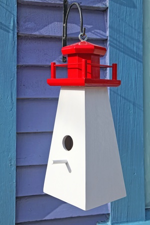 A hand crafted wooden birdhouse in the shape of a typical Nova Scotia lighthouse.