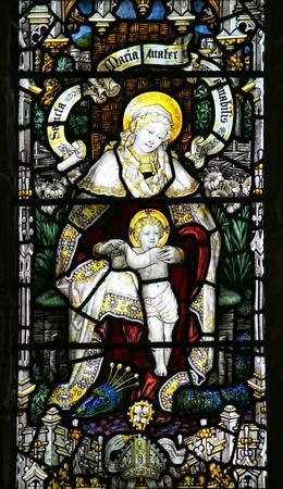 virgen maria: Virgen Mar�a y el ni�o Jes�s en la ventana de vidrio de color. Foto de archivo