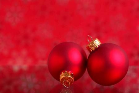 Red glass Christmas ornaments on a red background.