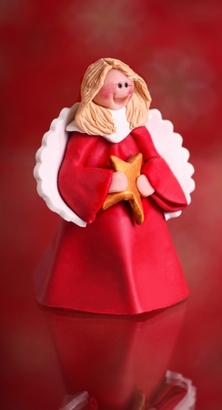 A little Christmas angel ornament on a red background.