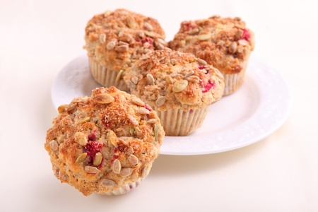 A plate full of homemade cranberry seed muffins full of pumpkin seeds, sunflower seeds and cranberriers. Stock Photo