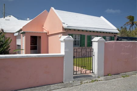 stucco: A traditional  Bermudian home and garden is surrounded by a stucco wall with a metal grill gate.