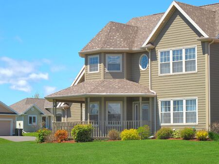 house siding: The front porch of a new two story family home in a residencial subdivision.