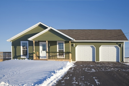 driveways: A small family home with a double car garage during the winter.