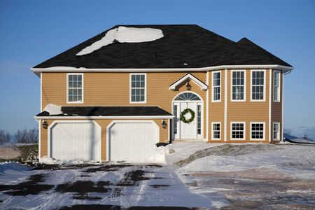 front: A large family home with a two car garage in the winter.