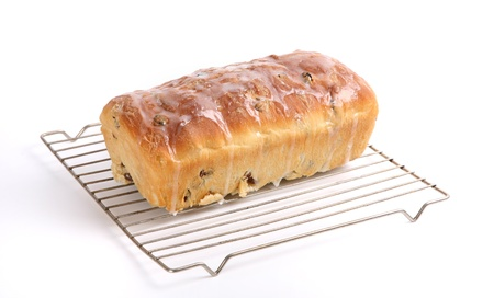 A loaf of homemade raisin bread decorated with an icing sugar glaze and sitting on a wire rack. Stock Photo