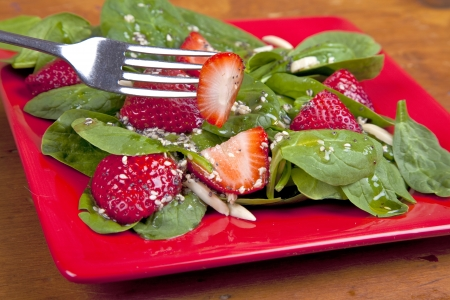 salad fork: Spinach strawberry salad with homemade dressing and almonds.