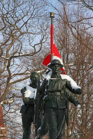 canadian flag: Snow covered war memorial of World War 1 soldiers with a Canadian Flag in the background.  Located in Charlottetown, Prince Edward Island, Canada. Editorial