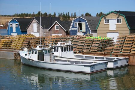 Fishing boats tied up to the wharf which is laden with lobster traps.