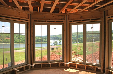 window pane: The interior of a partially constructed house showing the new windows and a lovely river view.