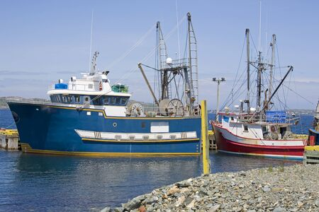 Fishing boats, one of which is a scallop dragger, at a wharf in Cupids, Newfoundland, Canada.