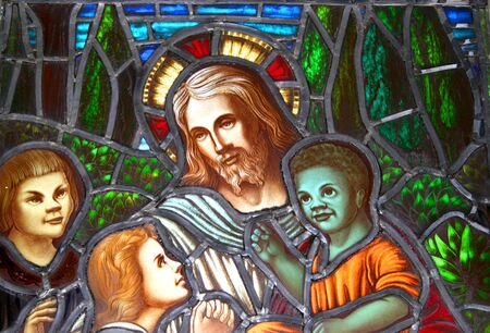 christ the king: A detail of a stained glass window circa 1899 showing Jesus surrounded by children of different ethnical backgrounds.